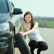 Woman changing car wheel — Stock Photo