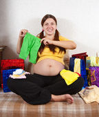 Pregnant woman with babies clothes — Stock Photo