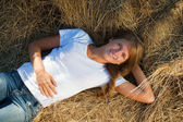 Girl laying on straw — Stock Photo