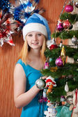 Girl in Santa hat near Christmas fir-tree — Stock Photo