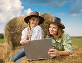 Country girls resting with laptop — Stock Photo