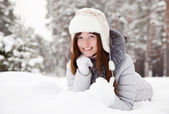 Young woman lying on snow — Stok fotoğraf