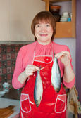 Woman with salty herring in hands — Stock Photo