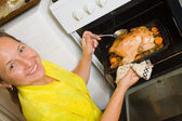 Woman roasting stuffed chicken — Stock Photo
