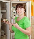 Woman putting with metal can near fridge — Stock Photo
