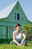 Happy woman on lawn in front of home — Stock Photo