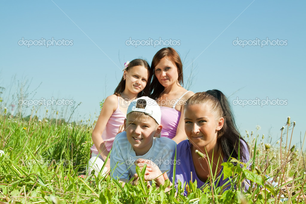 Two women with teens laying on the green grass — Stock Photo #6044075