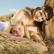 Stock Photo: Girls laying on hay