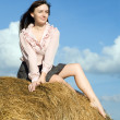 Stock Photo: Girl sitting on top of hay bail