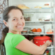 Mature woman putting pan into refrigerator - 图库照片