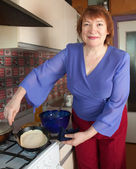 Mature woman bakes pancakes — Stock Photo