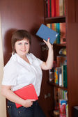 Woman selecting book — Stockfoto
