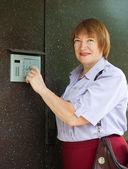 Mature woman dialing an intercom — Stock Photo