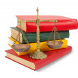Scales of justice atop legal books over white — Stock Photo