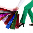 Beautiful stylish woman pulling shopping bags — Stock Photo