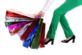 Beautiful stylish woman pulling shopping bags — Stock Photo