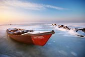 Red boat on sunset — Stockfoto