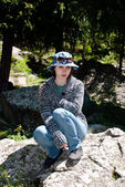 Beautiful woman sits on a rock — Stock Photo