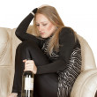 Girl with a bottle sitting on the couch — Stock Photo