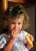 Little girl eating croissant — Foto Stock