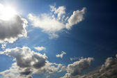 Clouds and sun on blue sky — Stock Photo
