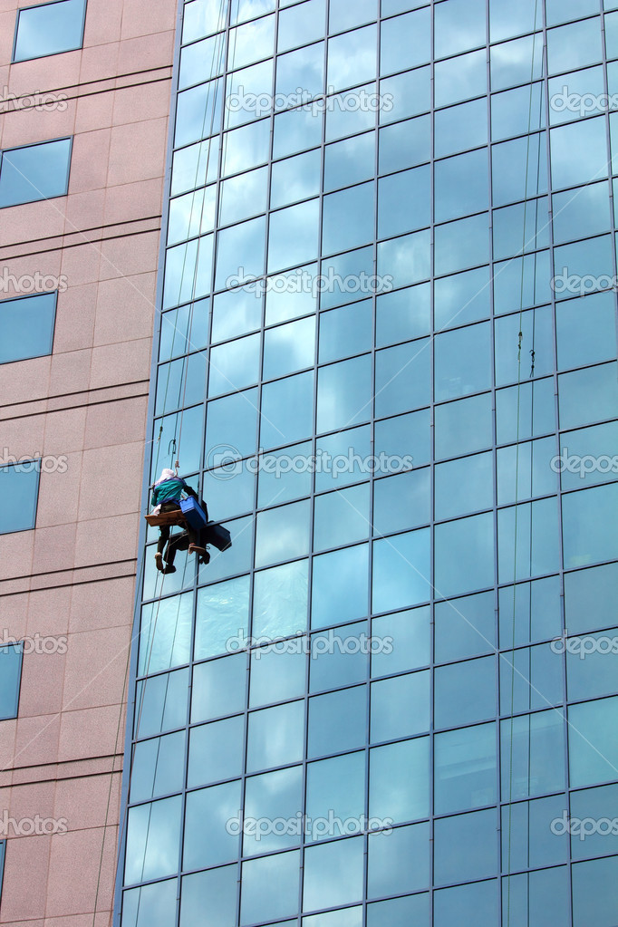 Window cleaner hanging on rope at work on skyscraper — Stock Photo #6109361