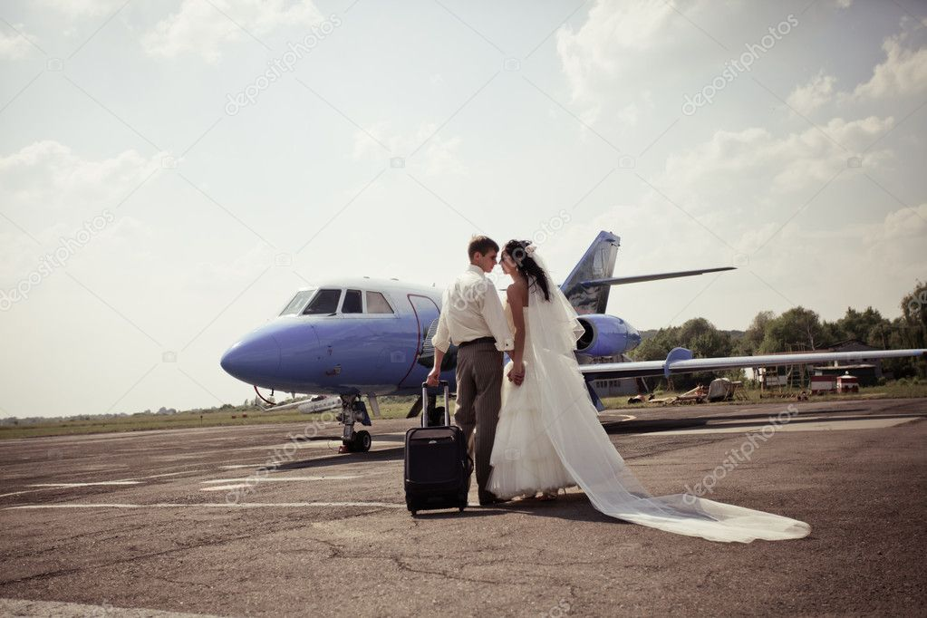 Wedding couple are prepare to fly on a honeymoon trip — Stock Photo #6056055