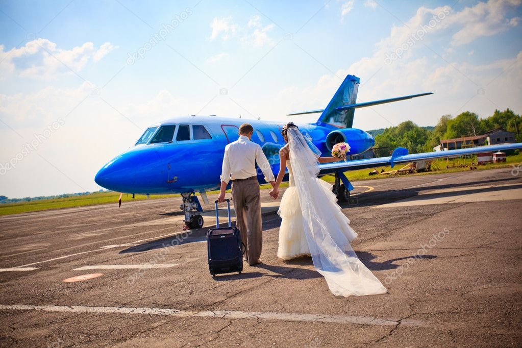 Wedding couple are prepare to fly on a honeymoon trip — Photo #6056056