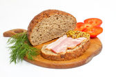 Bread with ham, mustard, dill and tomato on the wood plate — Stock Photo