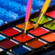 Palette of watercolor paints with three brushes — Stock Photo
