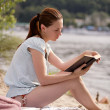 Young girl reading the book on the riverside — Stockfoto
