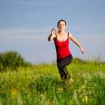 Woman running on a sunset field — Stock Photo