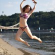 Woman jumping on the river beach — Stock Photo #6580747