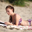 Woman reading magazine at the beach — Stock Photo