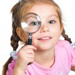 Little girl looking through a magnifier - Stock Photo
