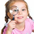 Little girl looking through a magnifier — Stock Photo