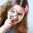 Little girl looking through a magnifying glass — Stock Photo