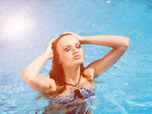 Woman with the background of a pool behind — Stock Photo