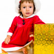 Little girl in santa hat with presents — Stock Photo #6349771