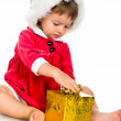 Little girl in santa hat with presents — Stock Photo