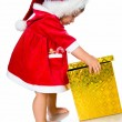 Little girl in santa hat with presents - Stock Photo