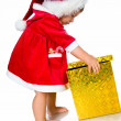 Little girl in santa hat with presents — Stock Photo #6406434