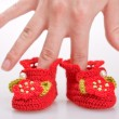 Crocheted booties for a girl in the woman hand - Stock Photo