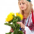 Woman wears Ukrainian dress is holding a sunflower - Stock Photo