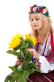 Woman wears Ukrainian dress is holding a sunflower — Stock Photo