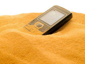 Mobile phone in sand isolated on white background. — Stock Photo