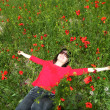 Woman lying in a field of poppies — Stock fotografie