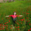 Woman lying in a field of poppies — Stock Photo