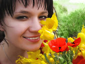 Woman smelling flowers — Stock Photo