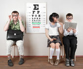 Three person wearing spectacles in an office at the doctor — Stock Photo